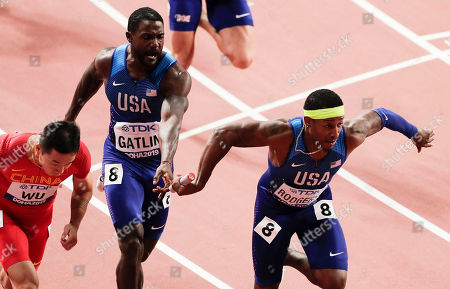 Justin Gatlin of the United States, center, passes the baton to Michael Rodgers in the men's 4x100 meter relay final at the World Athletics Championships in Doha, Qatar