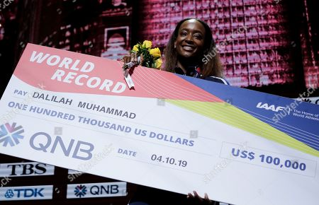 Dalilah Muhammad of the United States, gold, holds the cheque presented to her for her world record during the medal ceremony for the women's 400m hurdles at the World Athletics Championships in Doha, Qatar