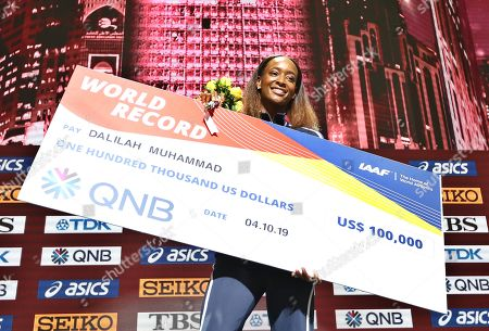 Gold medalist Dalilah Muhammad of the USA poses with her cheque she received for her world record during the medal ceremony for the women's 400m Hurdles at the IAAF World Athletics Championships 2019 at the Khalifa Stadium in Doha, Qatar, 05 October 2019.