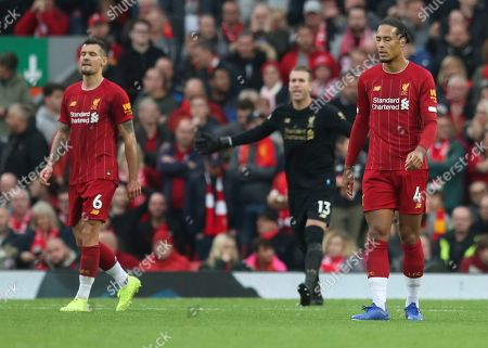 Liverpool's Virgil van Dijk, right, Liverpool's Dejan Lovren, left, and Liverpool's goalkeeper Adrianlooks on after Leicester City's James Daniel Maddison scored a goal during English Premier League soccer match between Liverpool and Leicester City in Anfield stadium in Liverpool, England