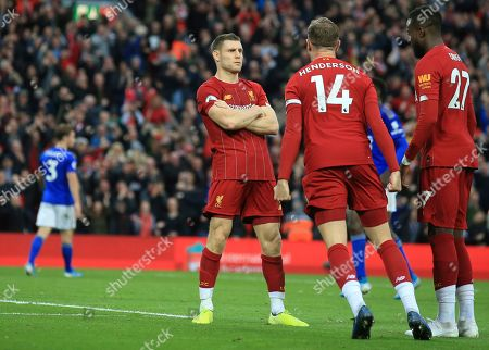 Liverpool's James Milner celebrates his wining goal with Liverpool's Jordan Henderson and Liverpool's Divock Origi during English Premier League soccer match between Liverpool and Leicester City in Anfield stadium in Liverpool, England