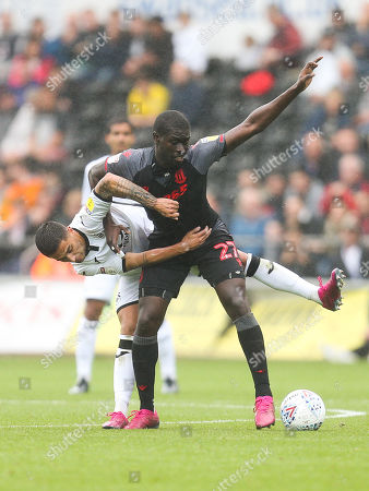 Badou Ndiaye of Stoke City and Yan Dhanda of Swansea City compete for the ball