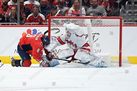Washington Capitals left wing Alex Ovechkin, left, of Russia, collides with Carolina Hurricanes goaltender James Reimer (47) during the first period of an NHL hockey game, in Washington