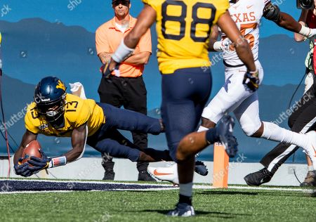 West Virginia wide receiver Sam James (13) catches a touch pass during the first half of an NCAA college football game Saturday against Texas, in Morgantown, W.Va