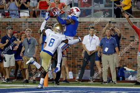 SMU wide receiver James Proche, in blue, catches a touchdown pass while Tulsa safety Brandon Johnson (8) defends during the third overtime of an NCAA college football game, in Dallas, Texas. SMU beat Tulsa 43-37