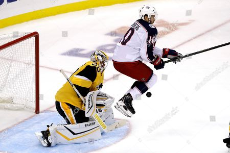 Columbus Blue Jackets' Alexander Wennberg (10) leaps to avoid a shot in front of Pittsburgh Penguins goaltender Matt Murray during the first period of an NHL hockey game in Pittsburgh