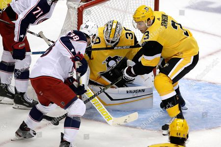 Pittsburgh Penguins' Jack Johnson (3) clears the puck from in front of goaltender Matt Murray (30) before Columbus Blue Jackets' Boone Jenner (38) can get a his stick on it during the first period of an NHL hockey game in Pittsburgh