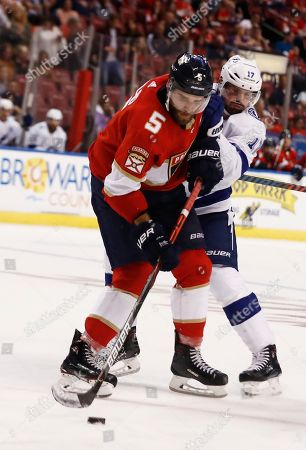 Florida Panthers defenseman Aaron Ekblad (5) and Tampa Bay Lightning left wing Alex Killorn (17) go for the puck during the second period of an NHL hockey game, in Sunrise, Fla