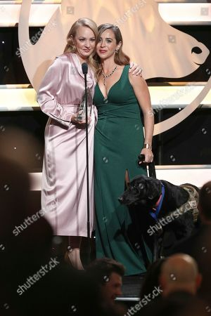 Wendi McLendon-Covey, Caroline Zuendel, Sgt. Yeager. Wendi McLendon-Covey, left, presents Caroline Zuendel and her dog Sgt. Yeager, with the military dog of the year award at the 2019 American Humane Hero Dog Awards at The Beverly Hilton, in Beverly Hills, Calif. The 2019 American Humane Hero Dog Awards airs October 21, at 8pm ET/PT on Hallmark Channel