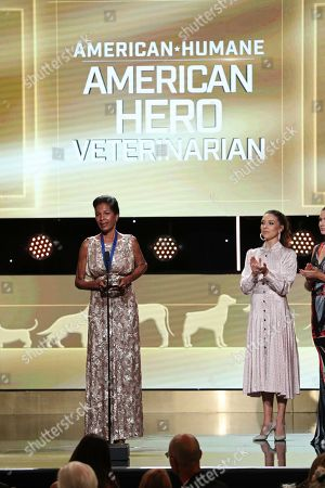 Stock Picture of Jenna Johnson, Dr. Terry Morris. Dr. Terry Morris, accepts the award for American Hero Veterinarian, at the 2019 American Humane Hero Dog Awards at The Beverly Hilton, in Beverly Hills, Calif. Jenna Johnson look on from stage right. The 2019 American Humane Hero Dog Awards airs October 21, at 8pm ET/PT on Hallmark Channel