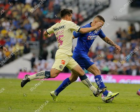 Cruz Azul's Jonathan Rodriguez, right, fights for the ball against America's Fernando Gonzalez during a Mexican soccer league match at Azteca Stadium in Mexico City