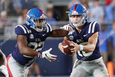 Stock Picture of Mississippi quarterback John Rhys Plumlee (10) hands off to running back Scottie Phillips (22) during the first half of their NCAA college football game in Oxford, Miss