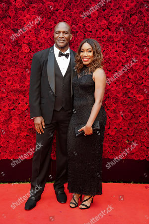 Evander Holyfield and guest pose for a photo on the red carpet at the grand opening of Tyler Perry Studio, in Atlanta