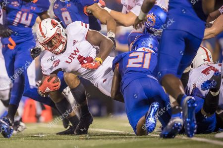 Stock Image of Incarnate Word Cardinals running back Kevin Brown (4) lunges for positive yardage during the NCAA football game between the Incarnate Word Cardinals and the Houston Baptist Huskies at Husky Stadium in Houston, Texas. Incarnate Word defeated Houston Baptist 38-36. Prentice C