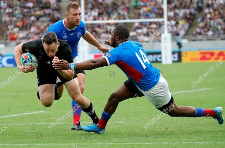 New Zealand's Ben Smith, left, steps inside the tackle of Namibia's Lesley Klim to score a try during the Rugby World Cup Pool B game at Tokyo Stadium between New Zealand and Namibia in Tokyo, Japan