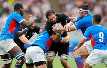 New Zealand's Samuel Whitelock, centre, runs at the Namibian defence during the Rugby World Cup Pool B game at Tokyo Stadium between New Zealand and Namibia in Tokyo, Japan