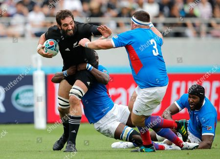 New Zealand's Samuel Whitelock looks to fend off Namibia's AJ De Klerk, right, during the Rugby World Cup Pool B game at Tokyo Stadium between New Zealand and Namibia in Tokyo, Japan