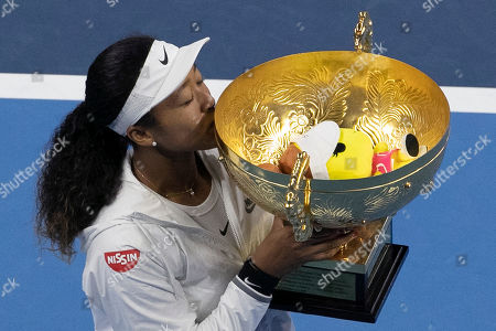 Naomi Osaka of Japan kisses her winner's trophy after defeating Ashleigh Barty of Australia in the women's final at the China Open tennis tournament in Beijing