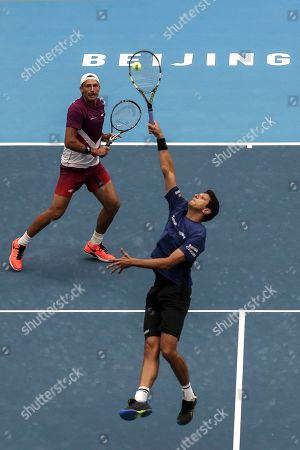 Lukasz Kubot, Marcelo Melo. Lukasz Kubot of Poland watches her partner Marcelo Melo of Brazil hits a return shot against Ivan Dodig of Croatia and Filip Polasek of Slovakia during the men's doubles final in the China Open tennis tournament in Beijing