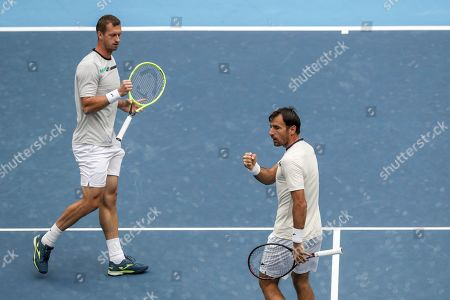 Ivan Dodig, Filip Polasek. Ivan Dodig of Croatia, right, and his partner Filip Polasek of Slovakia reacts as they competing against Lukasz Kubot of Poland and Marcelo Melo of Brazil in the men's doubles final of the China Open tennis tournament in Beijing