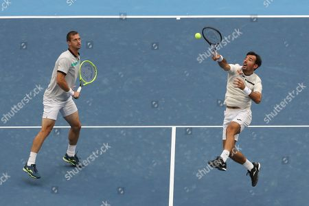 Ivan Dodig, Filip Polasek. Filip Polasek of Slovakia, right, and his partner Ivan Dodig of Croatia compete against Lukasz Kubot of Poland and Marcelo Melo of Brazil in the men's doubles final at the China Open tennis tournament in Beijing