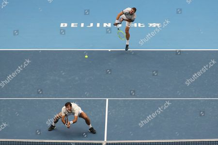Ivan Dodig, Filip Polasek. Filip Polasek of Slovakia, top, and his partner Ivan Dodig of Croatia compete against Lukasz Kubot of Poland and Marcelo Melo of Brazil in the men's doubles final at the China Open tennis tournament in Beijing