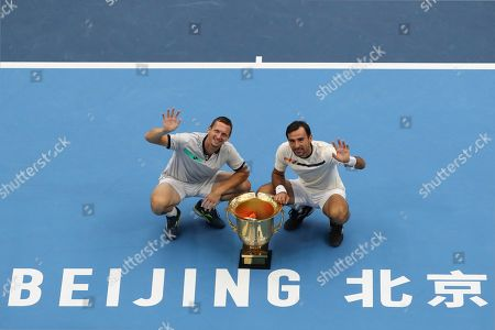 Ivan Dodig, Filip Polasek. Filip Polasek of Slovakia, right, and his partner Ivan Dodig of Croatia wave as they pose with their winner's trophy after defeating Lukasz Kubot of Poland and Marcelo Melo of Brazil in the men's doubles final at the China Open tennis tournament in Beijing