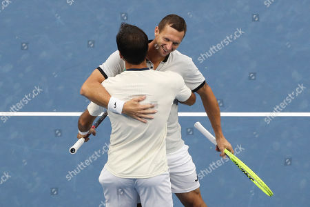 Ivan Dodig, Filip Polasek. Filip Polasek of Slovakia, foreground, celebrates with his partner Ivan Dodig of Croatia after defeating Lukasz Kubot of Poland and Marcelo Melo of Brazil in the men's doubles final at the China Open tennis tournament in Beijing