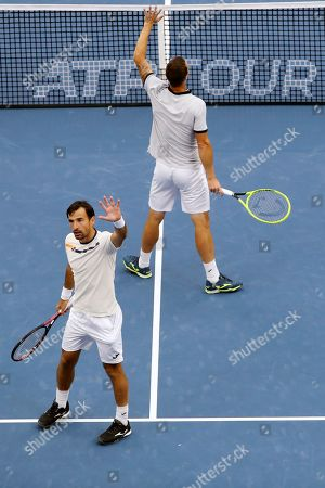 Ivan Dodig, Filip Polasek. Filip Polasek of Slovakia, foreground, and his partner Ivan Dodig of Croatia wave to spectators after defeating Lukasz Kubot of Poland and Marcelo Melo of Brazil in the men's doubles final at the China Open tennis tournament in Beijing