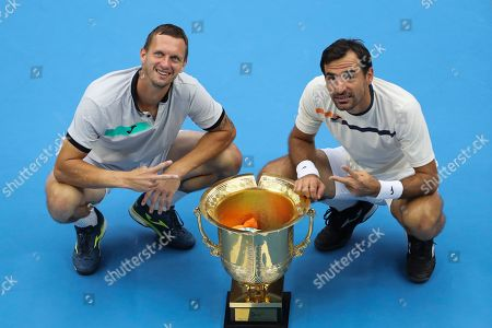 Ivan Dodig, Filip Polasek. Filip Polasek of Slovakia, right, and his partner Ivan Dodig of Croatia pose with their winner's trophy after defeating Lukasz Kubot of Poland and Marcelo Melo of Brazil in the men's doubles final at the China Open tennis tournament in Beijing