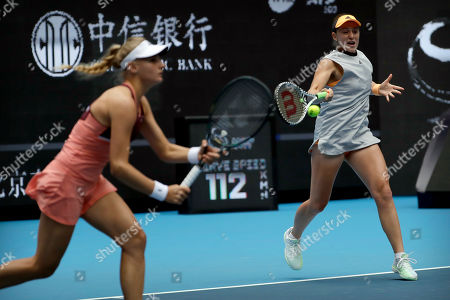 Jelena Ostapenko, Dayana Yastremska. Jelena Ostapenko of Latvia, right, hits a return shot while competing with partner Dayana Yastremska of Ukraine against Sofia Kenin and Bethanie Mattek-Sands of the United States in the women's doubles final at the China Open tennis tournament in Beijing