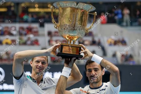 Ivan Dodig, Filip Polasek. Filip Polasek of Slovakia, right, and his partner Ivan Dodig of Croatia hold their trophy after defeating Lukasz Kubot of Poland and Marcelo Melo of Brazil in the men's doubles final at the China Open tennis tournament in Beijing