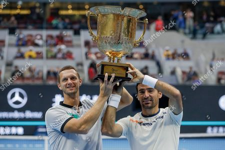 Ivan Dodig, Filip Polasek. Filip Polasek of Slovakia, right, and his partner Ivan Dodig of Croatia hold their winner's trophy after defeating Lukasz Kubot of Poland and Marcelo Melo of Brazil in the men's doubles final at the China Open tennis tournament in Beijing