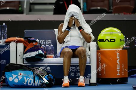 Naomi Osaka of Japan sits with a towel over her head during a break in play while competing against Ashleigh Barty of Australia during their women's final at the China Open tennis tournament in Beijing