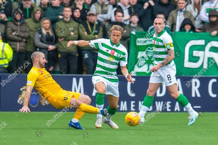 Scott Robinson (#17) of Livingston FC tackles Mortiz Bauer (#13) of Celtic FC, as Scott Brown (#8) of Celtic FC watches on during the Ladbrokes Scottish Premiership match between Livingston FC and Celtic FC at The Tony Macaroni Arena, Livingston