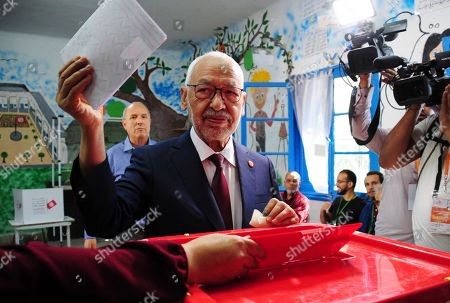 President of the Islamist party Ennahda and candidate for the Parliamentary election Rached Ghannouchi votes in a polling station south of Tunis, Tunisia, . Tunisians are electing a new parliament Sunday amid a tumultuous political season, with a moderate Islamist party and a jailed tycoon's populist movement vying to come out on top of a crowded field