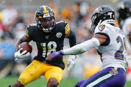 Pittsburgh Steelers wide receiver Diontae Johnson (18) tries to evade Baltimore Ravens free safety Earl Thomas (29) during the second half of an NFL football game, in Pittsburgh