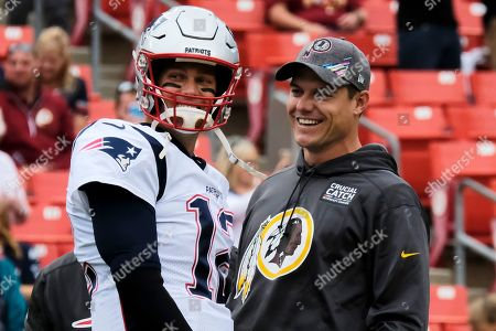 New England Patriots quarterback Tom Brady (left) and Washington Redskins offensive coordinator Kevin O'Connell (right) stand on the field prior to during an NFL football game between the New England Patriots and Washington Redskins, in Landover, Md
