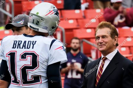 New England Patriots quarterback Tom Brady (left)) and Joe Theismann (right) talk on the field prior to an NFL football game between the New England Patriots and Washington Redskins, in Landover, Md
