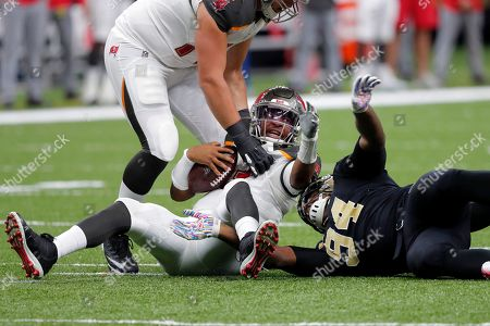 Tampa Bay Buccaneers quarterback Jameis Winston, let, reacts after being sacked by New Orleans Saints defensive end Cameron Jordan (94) in the second half of an NFL football game in New Orleans