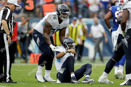 Tennessee Titans quarterback Marcus Mariota (8) is helped up by offensive guard Rodger Saffold (76) in the first half of an NFL football game against the Buffalo Bills, in Nashville, Tenn