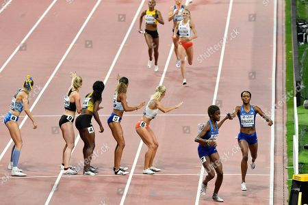 Gold medalists Dalilah Muhammad passes the baton to Wadeline Jonathas of the United States, bottom right, as they build up a lead on other competitors during the women's 4x400 meter relay final at the World Athletics Championships in Doha, Qatar