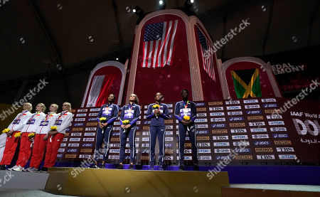 U.S. gold medalists from left, Phyllis Francis, Sydney Mclaughlin, Dalilah Muhammad and Wadeline Jonathas, stand on the podium during the medal ceremony for women's 4x400 meter relay final at the World Athletics Championships in Doha, Qatar, . At left is the Polish team who took the silver and an empty podium for bronze medalists Jamaica who did not show up