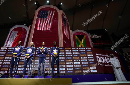 U.S. gold medalists from left, Phyllis Francis, Sydney Mclaughlin, Dalilah Muhammad and Wadeline Jonathas, stand on the podium during the medal ceremony for the women's 4x400 meter relay final at the World Athletics Championships in Doha, Qatar, . At right is an empty podium for bronze medalists from Jamaica who did not show up