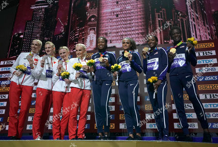 U.S. gold medalists from center, Phyllis Francis, Sydney Mclaughlin, Dalilah Muhammad and Wadeline Jonathas, stand with the silver medalists Poland during the medal ceremony for women's 4x400 meter relay final at the World Athletics Championships in Doha, Qatar, . Bronze medalists were from Jamaica, who did not show up
