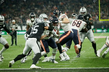 Chicago Bears running back David Montgomery (32) goes in for a touchdown against Oakland Raiders free safety Erik Harris (25) during the second half of an NFL football game at Tottenham Hotspur Stadium, in London