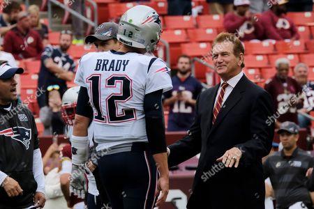 New England Patriots quarterback Tom Brady (12) speaks with former NFL player Joe Theismann ahead of an NFL football game between the Washington Redskins and the New England Patriots, in Washington