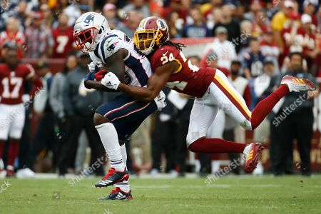 Stock Image of Washington Redskins cornerback Josh Norman (24) tacklesNew England Patriots running back Sony Michel (26) during the second half of an NFL football game, in Washington
