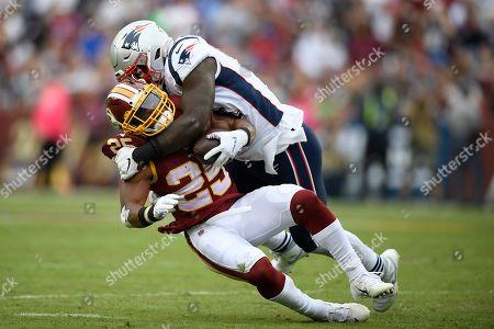 New England Patriots linebacker Ja'Whaun Bentley (51) hits Washington Redskins running back Chris Thompson (25) during the second half of an NFL football game, in Washington