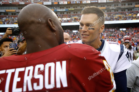 New England Patriots quarterback Tom Brady speaks with Washington Redskins running back Adrian Peterson after an NFL football game, in Washington. The New England Patriots won 33-7